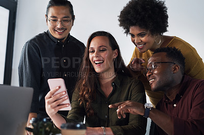 Buy stock photo Cropped shot of a diverse group of businesspeople looking at a cellphone together in the office