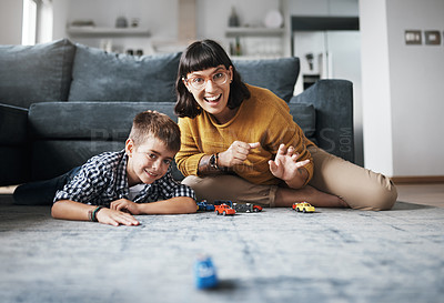 Buy stock photo Shot of a mother and her little son playing with toy cars together at home
