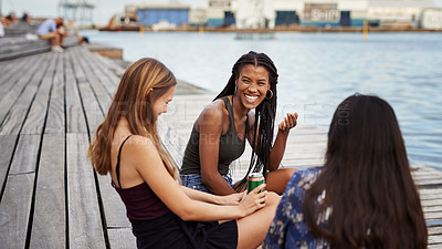 Buy stock photo Cropped shot of three attractive young friends sitting on the deck together and bonding during a day by the canal
