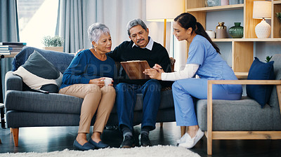 Buy stock photo Shot of a elderly couple having a discussion with a young medical practitioner while being seated on a sofa at home during the day