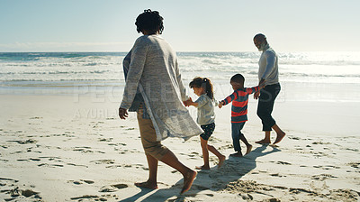 Buy stock photo Full length shot of a senior couple walking along the beach and holding hands with their grandchild and his friend