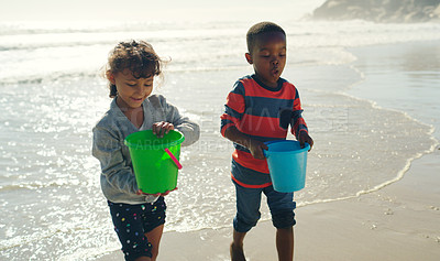 Buy stock photo Cropped shot of two young children carrying buckets filled with water before building sandcastles on the beach