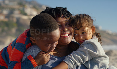 Buy stock photo Cropped shot of an attractive senior woman hugging her grandchildren as they sit on the beach in the afternoon