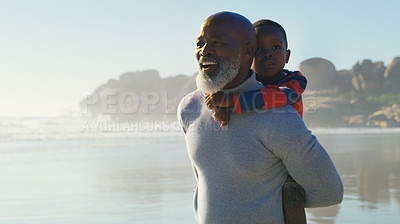 Buy stock photo Cropped shot of a happy senior man bonding with his cute grandson and giving him a piggyback on the beach