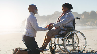 Buy stock photo Full length shot of an attractive senior woman sitting in a wheelchair as her husband kneels beside her outside