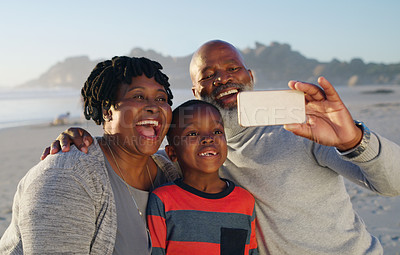 Buy stock photo Cropped shot of a happy senior couple using a cellphone to take a selfie with their grandson on the beach