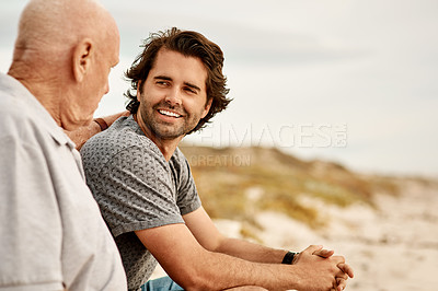 Buy stock photo Shot of a handsome young man spending the day with his father at the beach