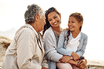 Buy stock photo Shot of an adorable little girl spending the day with her mother and grandmother at the beach