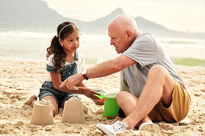 Buy stock photo Full length shot of an adorable little girl playing with her grandfather in the sand at the beach