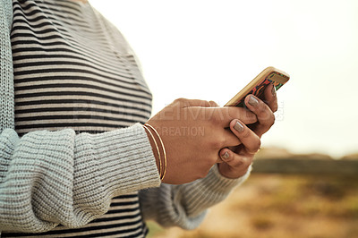 Buy stock photo Shot of an unrecognizable woman using her cellphone while relaxing in the outdoors