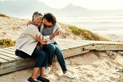Buy stock photo Shot of a senior woman and her adult daughter hugging and embracing while spending the day together at the beach
