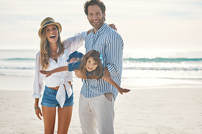 Buy stock photo Cropped portrait of an affectionate couple playing with their daughter during an enjoyable day out on the beach