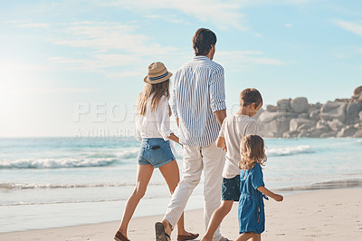 Buy stock photo Rearview shot of an unrecognizable couple holding hands with their two children and walking along the beach