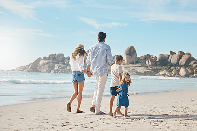 Buy stock photo Rearview shot of an unrecognizable couple holding hands with their two young children and walking along the beach