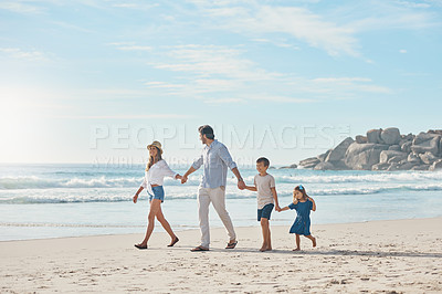 Buy stock photo Full length shot of a happy couple holding hands with their two young children and walking along the beach