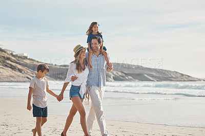 Buy stock photo Cropped shot of an affectionate couple holding hands with their two young children and walking along the beach