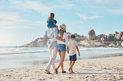 Buy stock photo Rearview shot of an affectionate couple holding hands with their two young children and walking along the beach