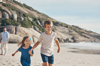 Buy stock photo Cropped shot of a happy young boy holding his little sister's hand and running along the beach with her