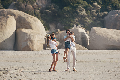 Buy stock photo Full length shot of a happy couple carrying and hugging their children during a day out on the beach