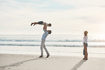 Buy stock photo Full length shot of a happy young couple bonding with their two young children during a day on the beach