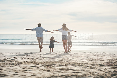 Buy stock photo Rearview shot of a happy young couple enjoying a playful day out with their two children on the beach
