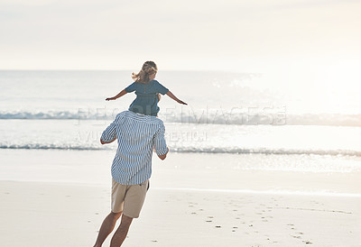 Buy stock photo Rearview shot of an unrecognizable father carrying his young daughter on his shoulders during an enjoyable day on the beach