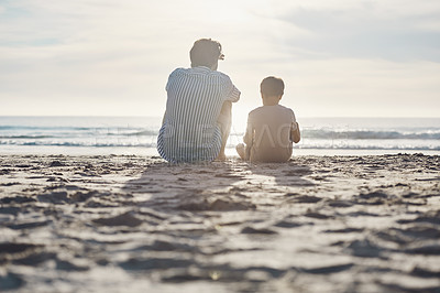 Buy stock photo Rearview shot of an unrecognizable father sitting and bonding with his son during an enjoyable day on the beach