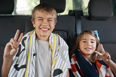 Buy stock photo Cropped portrait of two young siblings sitting in the car and making peace sign gestures before going on a roadtrip