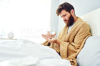 Buy stock photo Cropped shot of a young man taking medication at home