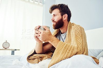 Buy stock photo Cropped shot of a young man having a cup of coffee while sitting in bed