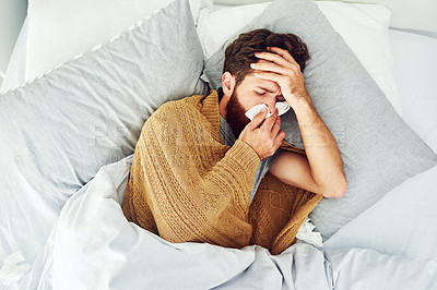 Buy stock photo Shot of a young man lying in bed while suffering with flu