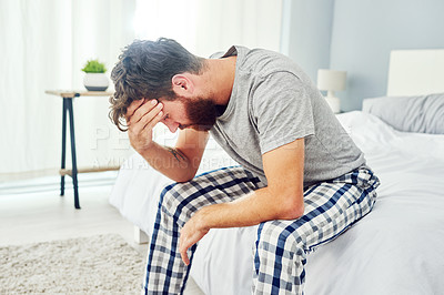 Buy stock photo Shot of a young man suffering from depression in his bedroom at home