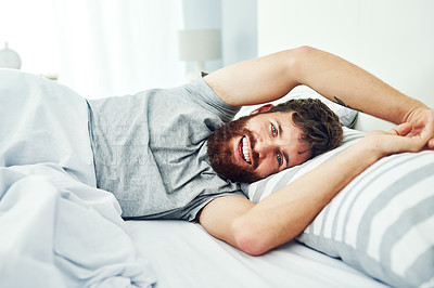 Buy stock photo Portrait shot of a young man smiling at the camera while lying in bed