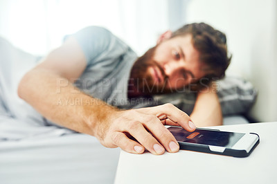Buy stock photo Cropped shot of a man looking at his cellphone on his bedside table while lying in bed