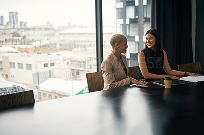 Buy stock photo Shot of two attractive young businesswomen having a meeting and discussing ideas in an office