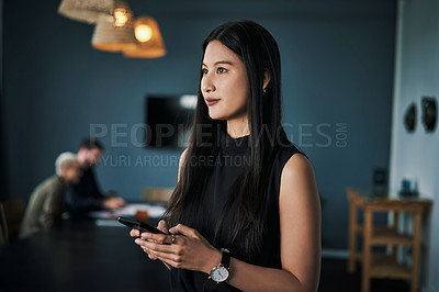 Buy stock photo Shot of an attractive young businesswoman using a cellphone in an office with her colleagues in the background