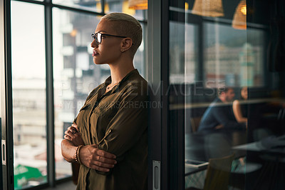 Buy stock photo Shot of an attractive young businesswoman looking thoughtful while standing inside an office with her colleagues in the background