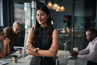 Buy stock photo Shot of an attractive young businesswoman standing inside an office with her colleagues working in the background