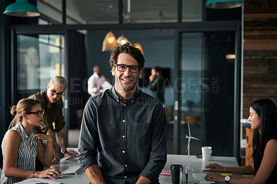Buy stock photo Portrait of a handsome businessman standing inside an office with his colleagues working in the background