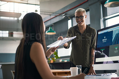 Buy stock photo Shot of an attractive young businesswoman handing over a document to her colleague at work