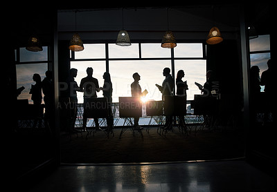 Buy stock photo Full length silhouetted shot of a group of businesspeople working and conversing together inside a modern office