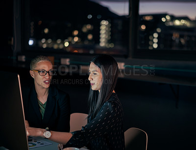 Buy stock photo Shot of two attractive young businesswomen using a computer together while working late inside their office