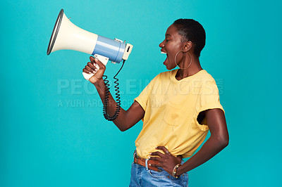 Buy stock photo Studio shot of a young woman using a megaphone against a turquoise background