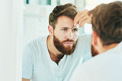 Buy stock photo Cropped shot of a handsome young man tweezing his eyebrows