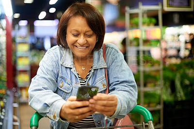 Buy stock photo Shot of a mature woman using her cellphone while out shopping in a grocery store