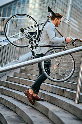 Buy stock photo Shot of a young businessman carrying his bicycle while walking up steps in a city