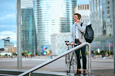 Buy stock photo Shot of a young businessman using a smartphone while traveling through the city with his bicycle