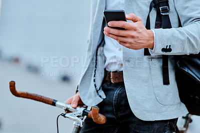 Buy stock photo Cropped shot of a businessman using a smartphone while traveling through the city with his bicycle