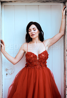 Buy stock photo Shot of a beautiful young woman dressed in elegant wear standing in a doorway outdoors