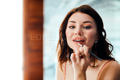 Buy stock photo Shot of a glamorous young woman applying lipstick with a brush in front of a mirror